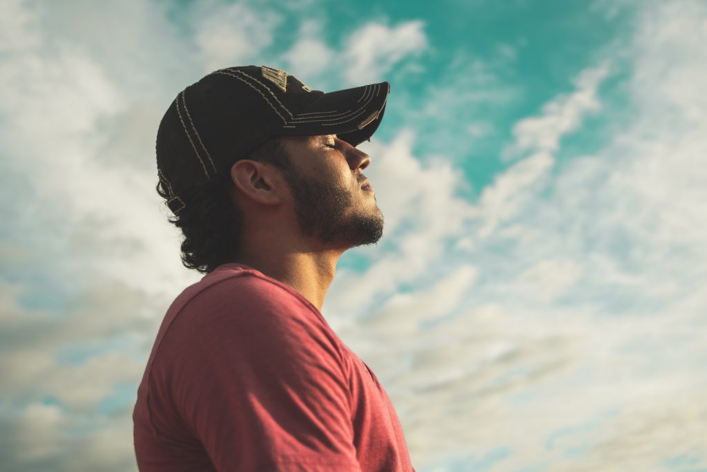man wearing black cap with eyes closed under cloudy sky 810775