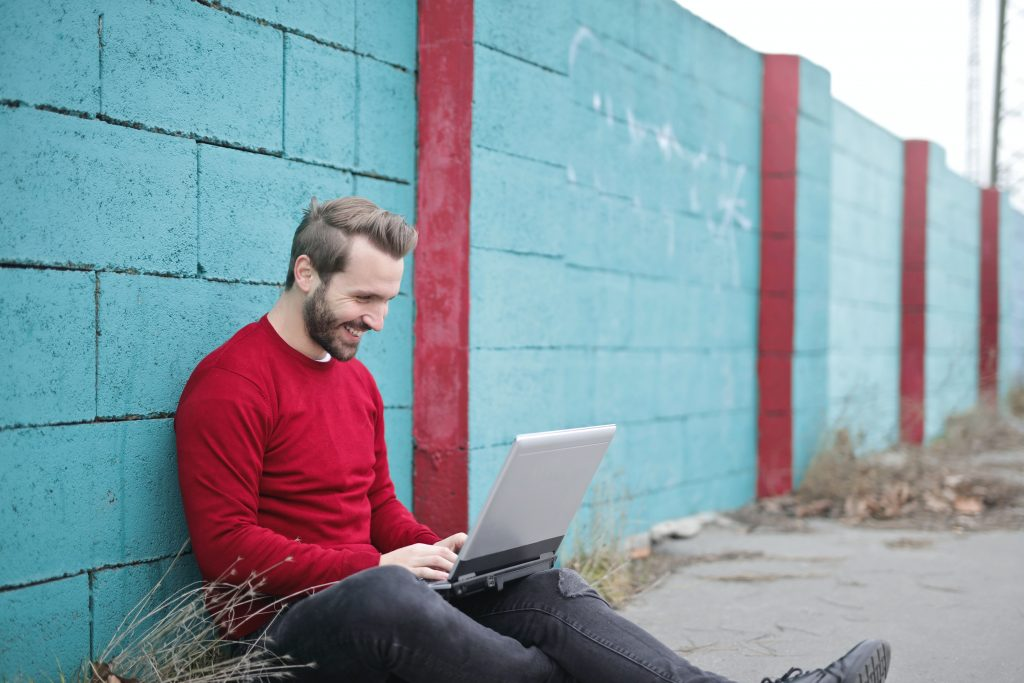 man leaning against wall using laptop 941572