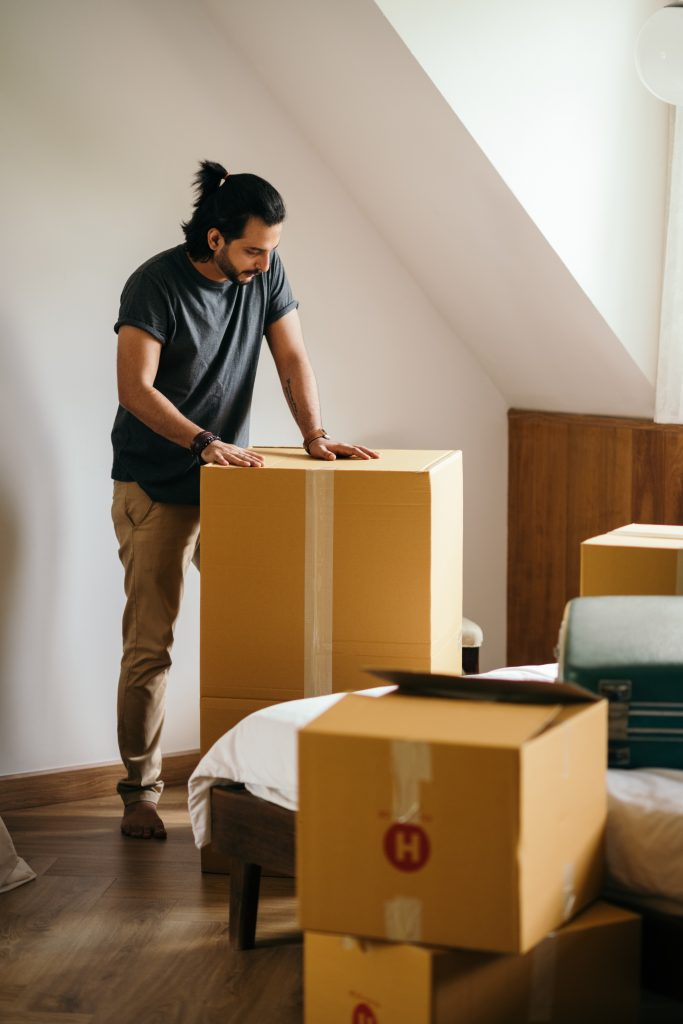 young man packing cardboard boxes at home 4247769